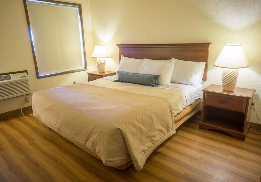 one queen bed with a nightstand on each side in room with window shade closed at Sunnyside Inn and Suites